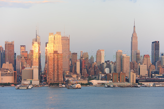The setting sun reflects off the windows of Manhattan skyscrapers on 42nd street as viewed over the Hudson River from New Jersey.