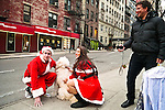 NEW YORK, NY - DECEMBER 15: Revelers dressed as Santa Claus get their picture taken with a dog on the street during the annual SantaCon event December 15, 2012 in New York City. (Photo by Donald Bowers)