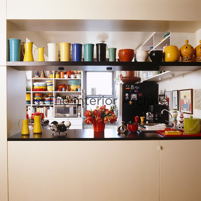 The open shelving in the kitchen is perfect for displaying the collection of colourful vintage Bauer pottery