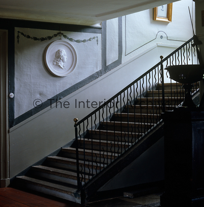 A round medaillion benath painted garlands overlooks this stone staircase with a wrought-iron banister