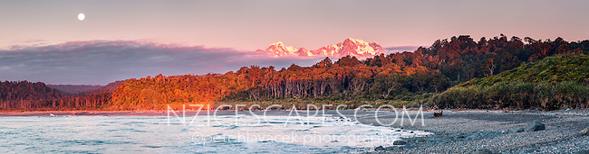Moonrise and sunset over Southern Alps mountains Mt. Cook 3754m right and Mt. Tasman 3497m left from Gillespies Beach, Westland National Park, World Heritage Area, West Coast, South Westland, South Island, New Zealand
