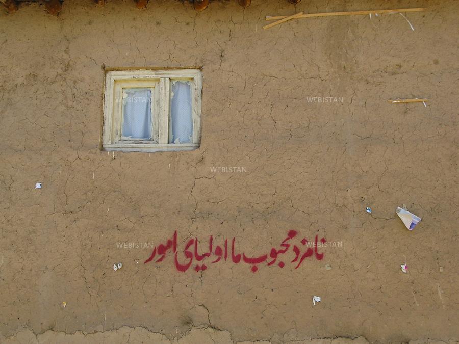 """AFGHANISTAN - VALLEE DU PANJSHIR - 18 aout 2009 : Slogan detourne dans le contexte des elections presidentielles afghanes de 2009. Il est ecrit : """"Notre cher candidat est le Saint des Saints"""". .La photographie appartient a la serie """"Le vote de la rue"""". ..AFGHANISTAN - PANJSHIR VALLEY - August 18th, 2009 : A slogan referring to the 2009 Afghan presidential elections painted on a wall. It reads: """"Our dear candidate is the Saint of Saints."""".The photograph is part of the series """"The Street Vote."""""""