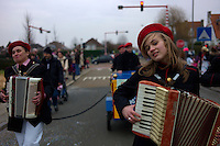 Musicians play the accordion during the Kraainem carnival parade on the edge of Brussels, Belgium on Feb. 16, 2013. Kraainem sits on the border between Dutch-speaking Flanders and Brussels, which has  a bilingual French-speaking majority. One of the curiosities along the language border is how the color of paint on traffic lights changes depending on the region. In Flanders, the lights are painted with black and yellow stripes to match the Flemish flag. In Brussels and Wallonia, the lights are painted red and white as seen in the background of this picture.