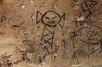 Precolumbian pictogram of an angry child by the indigenous Tainos culture, in the Cueva de la Linea or Cueva del Ferrocaril, created by limestone erosion, in the Parque Nacional de los Haitises, or Los Haitises National Park, on the North East coast of the Dominican Republic, in the Caribbean. The paintings were made using berry juice, mangrove bark, charcoal, manatee grease and bat droppings. The park was established in 1976 and consists of limestone karst scenery, mountains, subtropical forest and mangrove forests along the coast. Picture by Manuel Cohen
