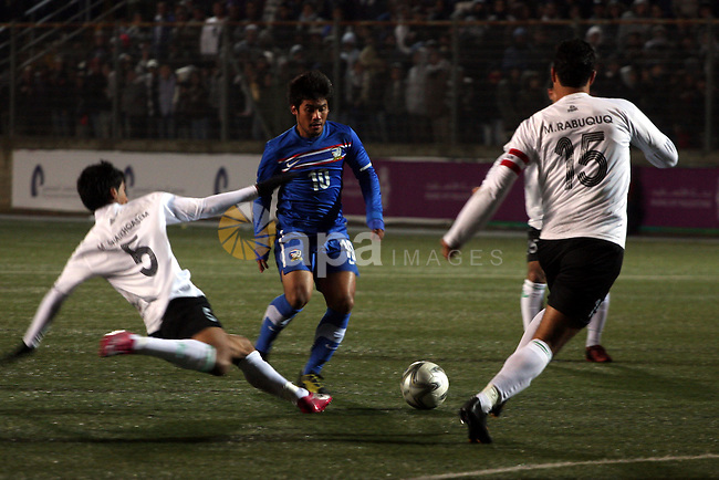Palestinian (white) and Thailand  national football players fight for the ball during their qualifier match for the Asian group of the 2012 London Olympics on March 9, 2011 at the Faisal Husseini stadium in the West Bank town of al-Ram between Ramallah and Jerusalem. The match is the first official international fixture to be hosted on Palestinian home soil. Thailand won 1-0. Photo by Issam Rimawi