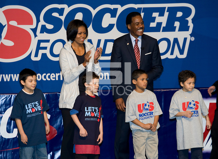 First Lady Michelle Obama and US Soccer President and CEO Ed Foster-Simeon watch a drill during a US Soccer Foundation clinic held at City Center in Washington, DC.