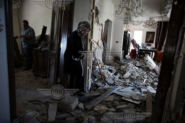 Mona Sabbagh, 55, surveys the damage to her apartment after it was hit by two unknown projectiles, in Damascus, Syria. The Syrian military claimed the projectiles were fired by rebels in the city's suburbs, but the scale of the destruction suggest possible stray Syrian army shells.