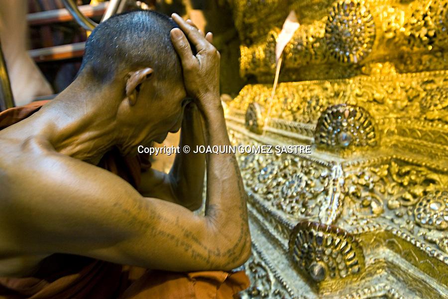 Monje budista rezando ante una imagen de un buda de oro en un templo en Myanmar.foto © JOAQUIN GOMEZ SASTRE