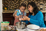 3 year old boy in kitchen at home with mother learning to cook baking, pouring non-dairy milk into measuring up
