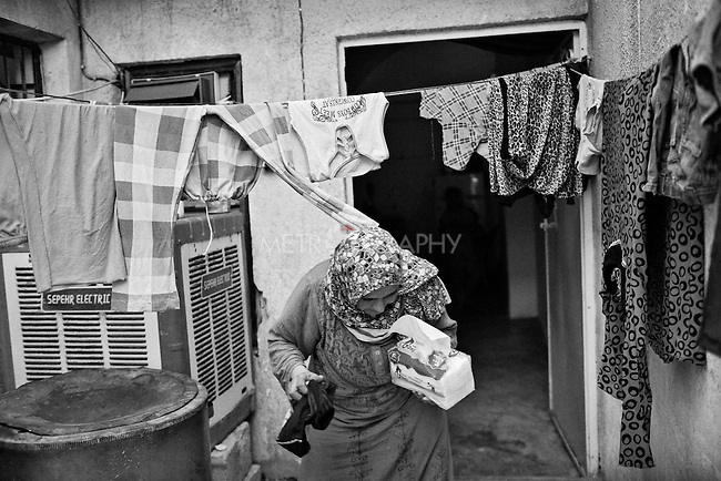 25..3.2015 Kirkuk, Iraq. Widad hanging the washed clothes on a rope in the court of the house she shares with her Christian neighbours.