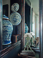 Displayed in an alcove are an eighteenth century Chinese ginger jar and plates, and a bronze Art Deco light