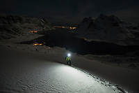 Female hiker hikes by headlamp through deep snow above Vindstad