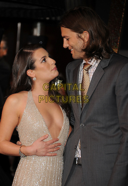 "Lea Michele & Ashton Kutcher.The World Premiere of ""New Year's Eve' held at The Grauman's Chinese Theatre in Hollywood, California, USA..December 5th, 2011.half length gold beige dress low cut plunging neckline cleavage grey gray suit jacket hand looking up down profile .CAP/ROT/TM.©Tony Michaels/Roth Stock/Capital Pictures"