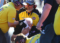 Oct 30, 2015; Las Vegas, NV, USA; NHRA safety safari personnel tend to crew member Barry Paton after being hit by the car of NHRA top fuel driver Tim Boychuk during qualifying for the Toyota Nationals at The Strip at Las Vegas Motor Speedway. Mandatory Credit: Mark J. Rebilas-USA TODAY Sports