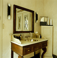 The walls and cabinet in the bathroom have been marbleised so that they blend with the marble of the antique washstand