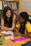 Education high school classroom scenes female teacher leaning in to talk to female student