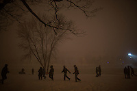 People walk along the Charles River bank in Cambridge, Massachusetts, USA, as Winter Storm Nemo approaches on Friday, Feb. 8, 2013.