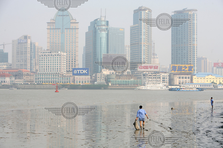 A worker picks up trash washed up onto the muddy banks of the Huangpu River in Shanghai. A recent survey of seven of China's major river systems by the nation's State Environmental Protection Administration showed 58 percent of China's water is grade three or below. And 28 percent of the water fell into grade five, unsuitable for even agricultural use. Of China's 662 major cities, 278 have no sewage treatment plants. Only 23 percent of China's sewage is treated while the rest is discharged into rivers and lakes.