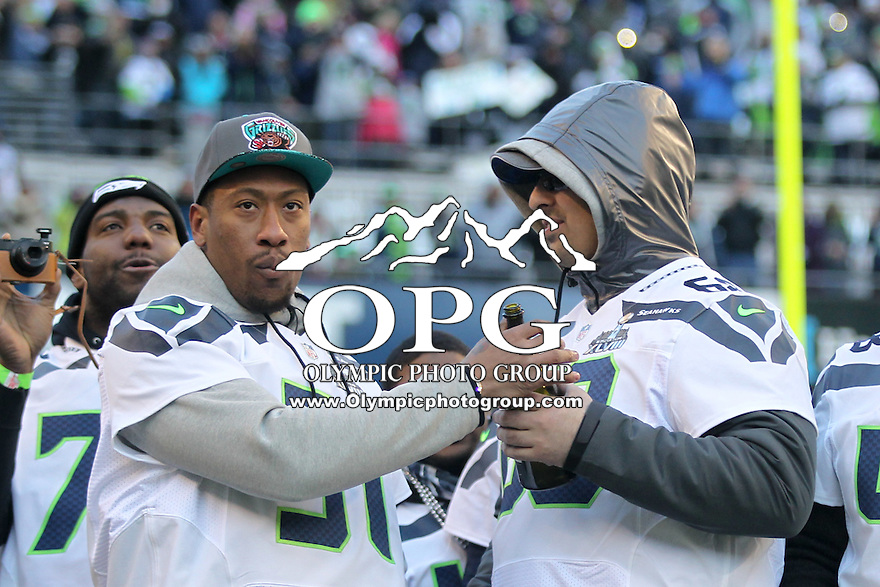 2014-02-05:  Seattle Seahawks Bruce Irvin and Breno Giacomini celebrated on stage with a bottle of champaign. Seattle Seahawks players and 12th man fans celebrated bringing the Lombardi trophy home to Seattle during the Super Bowl Parade at Century Link Field in Seattle, WA.