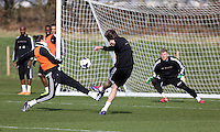 Pictured: Michu (C) goas for goal against David Cornell (R), Chico Flores attempts to tackle him (L). Saturday 08 March 2014<br /> Re: Swansea City FC training at the Fairwood Training ground in the outskirts of Swansea, south Wales.