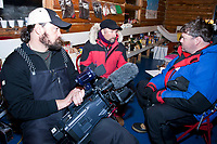The Iditarod Insider crew Kevin Bodhi, Bruce Lee and Greg Heister plan strategy inside the Community Center at the village of Ruby during the 2010 Iditarod