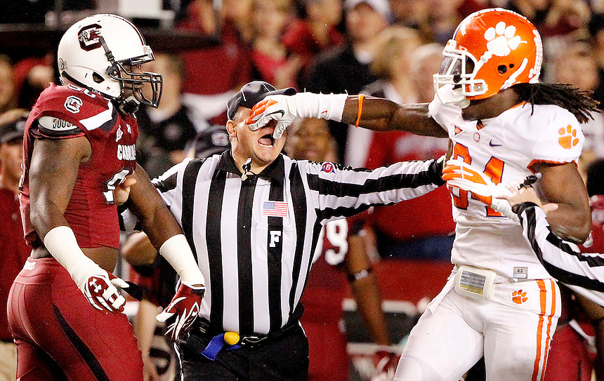 Field Judge Mike Cullin gets a slap to the face as he breaks up a scuffle between South Carolina's Chaz Sutton and Clemson's Quandon Christian after the opening kickoff on Nov. 26, 2011.
