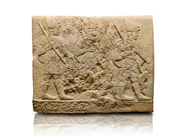 Hittite sculpted orthostats of Long Wall Limestone, Karkamıs, (Kargamıs), Carchemish (Karkemish), 900-700 BC. Anatolian Civilisations Museum, Ankara, Turkey<br /> <br /> Soldiers. Figure of three helmeted warriors. They have their shield in their back and their spear in their hand. The prisoners in their front are depicted as small. The lower part of the orthostat is decorated with wring / braiding motifs.<br /> <br /> On a White Background.