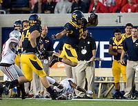 Daniel Lasco of California leaps over Ohio State defenders during the game at Memorial Stadium in Berkeley, California on September 14th, 2013.  Ohio State defeated California, 52-34.
