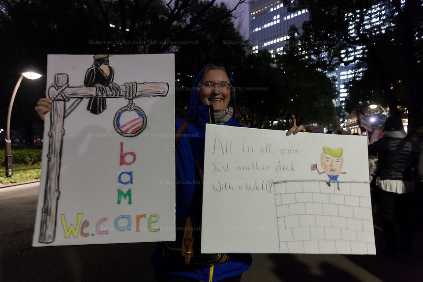 A holds signs mocking Donald Trump and his plans for The Affordable Care (Obamacare) at a protest march by members of the Democratic Party Abroad organisation to mark the inauguration of President Donald Trump, Tokyo, Japan. Friday January 20th 2017 Around 400 people took apart in the march, which started in Hibiya Park at 6:30pm and finished in Roppongi just before 8pm, to honour the service given by President Obama and to protest against the illiberal policies expected of the new administration of President  Trump.