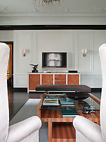 A pair of wing-backed armchairs in the living room frames a plasma screen and wood veneer sideboard on the far wall