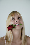 Close-up of a young woman holding a rose between teeth