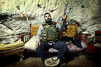 Photographer: Rick Findler..27.04.12 A member of the Free Syrian Army poses for a picture as he sits in a cave hidden in a mountain in Northern Syria. They have lived in the cave for the past three months but had only installed electricity yesterday. Most of the soldiers that sleep here are defectors of Assad's army.