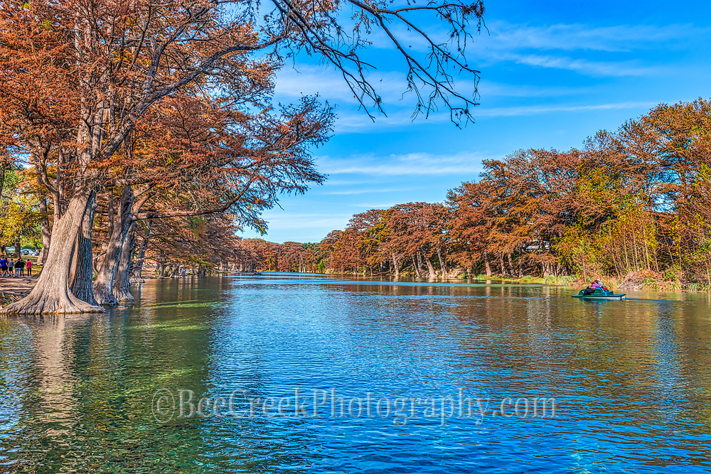 On a nice day on the Frio River in Garner State Park in the falls. This image of Garner as the leaves turned oranges, and reds, colors along the Frio River. are a nice backdrop against the blue green waters.  Many people come to Garner State Park year round for it beautiful clear waters and recreation that is available.  In the fall there is still plenty to do you can rent a paddle boat, kayak. hike, climb old baldy, ride horses, fish, camp and more. You see people out in the paddle boats on this wonderful day.