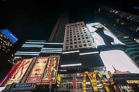 """Wearing wireless headsets, hundreds of visitors watch """"test pattern (times square)"""" by the artist Ryoji Ikeda while listening to the artist's composed soundtrack just before midnight on Thursday, October 16, 2014. As part of the """"Midnight Moment"""" the artist has taken over multiple screens in Times Square from 11:57 PM to midnight with his flickering images. A monthly event the Midnight Moment invites daily  three minute performances from artists every month. This is the first time sound has been incorporated into a viewing.  (© Richard B. Levine)"""