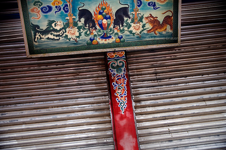 A colorful sign advertises a closed book shop in Xiahe, Gansu, China. Xiahe, home of the Labrang Monastery, is an important site for Tibetan Buddhists.  The population of the town is divided between ethnic Tibetans, Muslims, and Han Chinese.