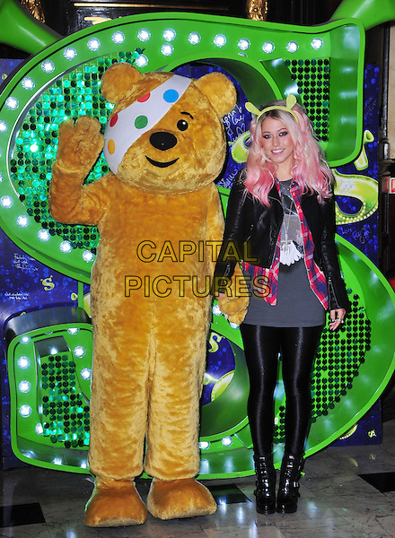 X Factor finalist Amelia Lily joins Pudsey Bear at Shrek The Musical at Theatre Royal Drury Lane, London, to celebrate her collaboration in this year's BBC Children in Need POP Goes the Musical.  On Wednesday 14th November, Amelia will take to the stage to perform a unique collaboration with cast members from the award-winning Shrek The Musical. Theatre Royal Drury Lane, London, England..October 29th, 2012.full length leather jacket grey gray top leggings hand waving costume  pink dyed hair streaks hairband green ears holding hands.CAP/BF.©Bob Fidgeon/Capital Pictures.