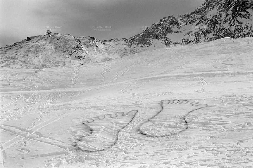 Switzerland. Ticino canton. Airolo. Winter season . Peschün ski resort. Footprints on the snow. Drawing of two feet in the snow. . The Yeti or Abominable Snowman is an ape-like creature taller than an average human. 8.03.2000 © 2000 Didier Ruef