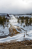 USA, Wyoming, Yellowstone National Park, steaming water spills into the Firehole River in the Upper Geyser Basin, Old Faithful, the Old Faithful Inn in the distance