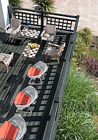 A black-stained terrace overhangs the garden and is furnished with a mixture of garden and Bertoia wire mesh chairs