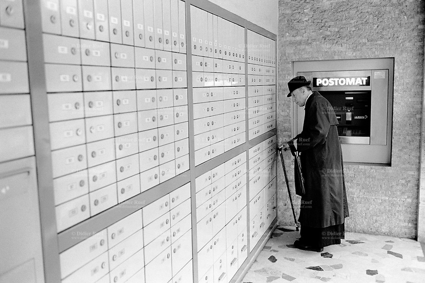 Switzerland. Canton Ticino. Massagno. Post office boxes. A catholic parish priest collects his mail at the P.O. box. Clerical dress. A postomat cash machine ( Post machine and cash poin ) is fixed on the wall. Massagno is 5 km distant from Lugano © 1999 Didier Ruef