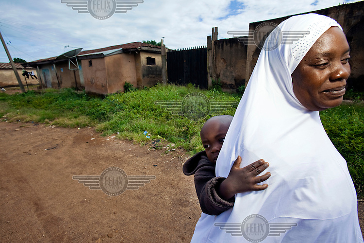 A woman carries her baby through the Dutse Uku district of the city, mostly inhabited by Muslims. Continued violence between Christians and Muslims has torn the city of Jos apart.