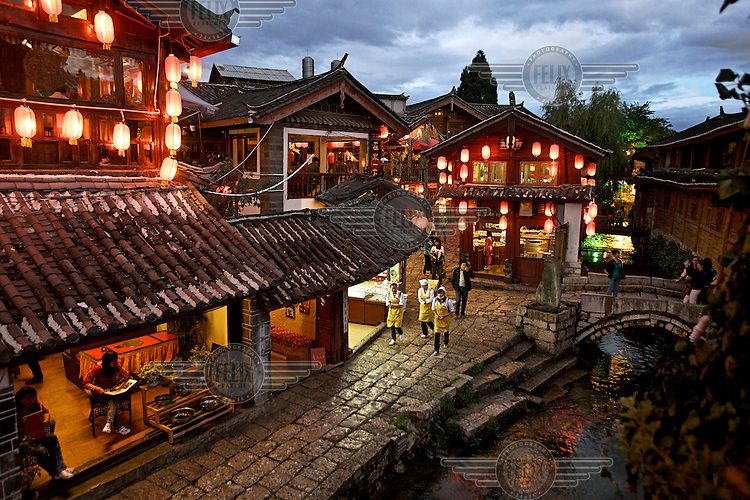 Waterside restaurants and shops, illuminated by lanterns, in Lijiang a town whose historic buildings are a major tourist attraction and an UNESCO World Heritage Site. /Felix Features