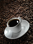 White cup of coffee with a saucer on coffee bean background