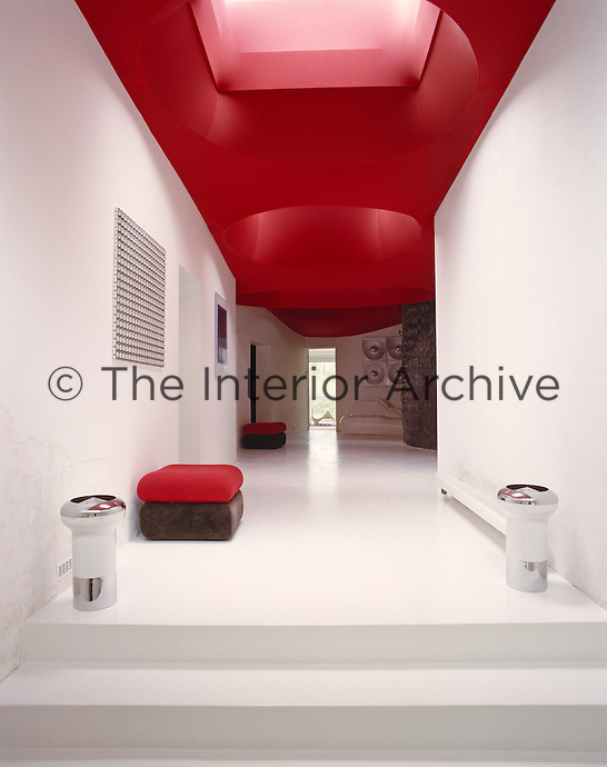 The blazing-red ceiling in the entrance hall of this 1970s house is pierced with large oval Perspex windows and is complimented with a white resin floor