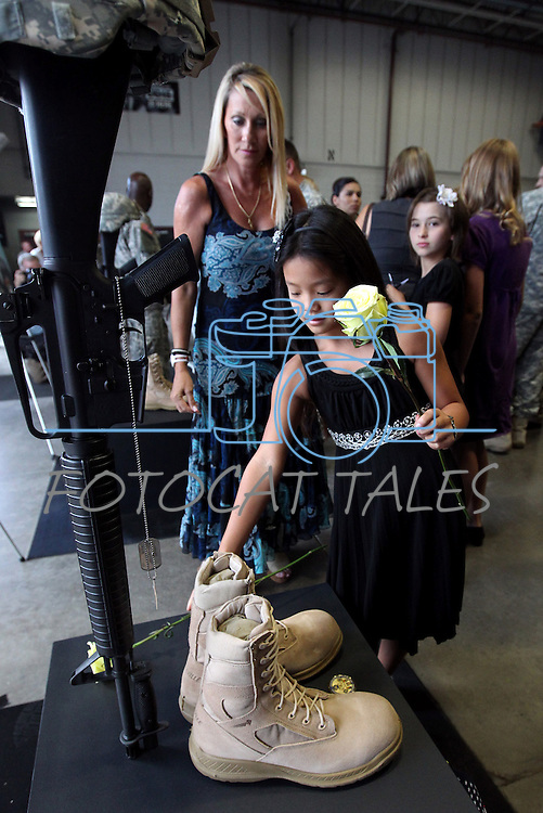 Christi Tanaka, 8, and her mom Sara lay roses on the memorials for three Nevada National Guard members killed earlier this week by a gunman in an IHOP restaurant. A private memorial service was held in Carson City, Nev., Sunday afternoon, Sept. 11, 2011. (AP Photo/Cathleen Allison)