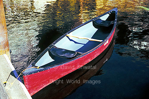 red canoe moored to a dock floats gently on calm tranquil lake water with reflection