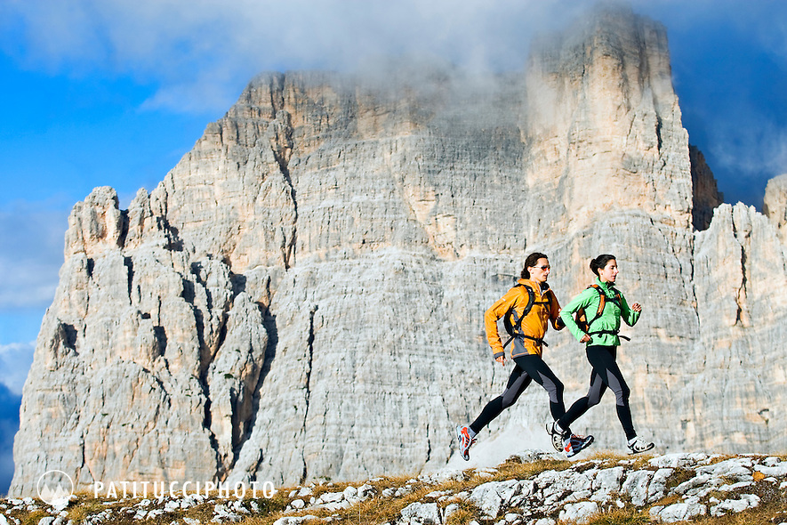 Filippo Tosoratti and Amy Fountain trail running at sunset on a cloudy day high in the Italian Dolomites
