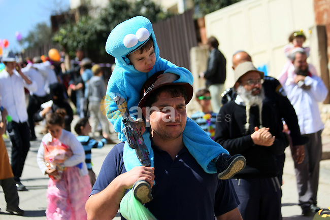 Israeli settlers attend celebrations marking the Jewish holiday of Purim in the occupied West Bank city of Hebron March 5, 2015. Purim is a celebration of the Jews' salvation from genocide in ancient Persia, as recounted in the Book of Esther. Photo by Mamoun Wazwaz