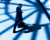 Blurred motion image of a businessman carrying a briefcase strides through a geometric pattern of shadows and blue light.