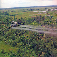 Vietnam. 07/26/1969- Defoliation Mission. A UH-1D helicopter from the 336th Aviation Company sprays a defoliation agent on a dense jungle area in the Mekong delta